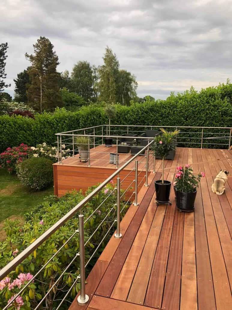 Forhøjet træterrasse med rækværk møbler og planter